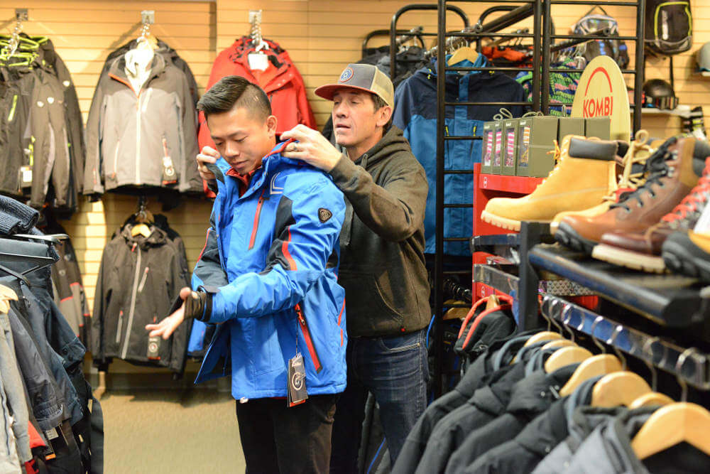 Customer buying men's ski outerwear from our shop in Banff, Alberta