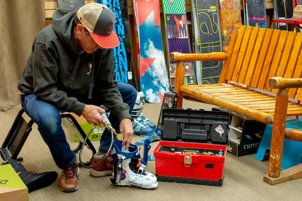Customer getting their ski boots expertly boot fitted by the staff at Abominable Sports in Banff, Alberta.